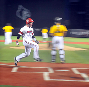 Kirk Gibson jumps on home plate for UofL's first run, thanks to a single by Nick Solac.