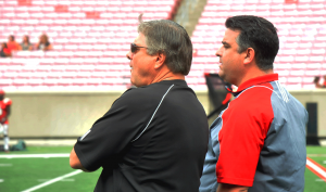 Tom Jurich and Rocco Gasparo watch the action.