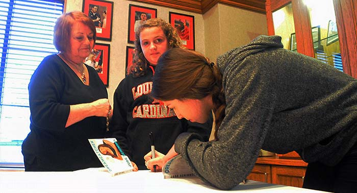 Jude Schimmel was kept busy signing books Sunday at the Cardinal Hall of Fame Cafe.