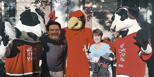 Long-time UofL fans Jerry and Yvonne Brumleve are joined by the Cardinal Bird and Chick-fil-A cows.