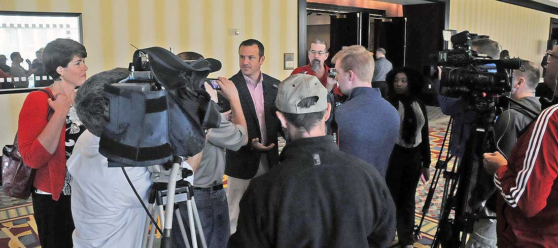 Jeff Walz is engulfed by media prior to UofL women's basketball tipoff luncheon.