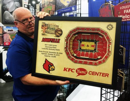 Ken Clark, of Dynogen Marketing, displays wall hanging of KFC Yum! Center.