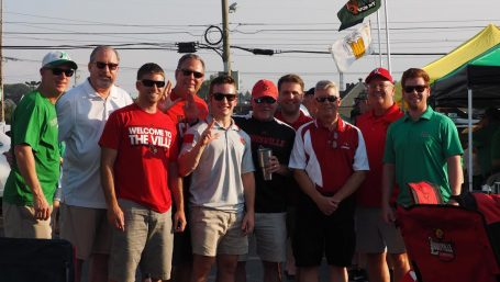 Joining a group of UofL tailgaters were Scott and Parker Ward (far left in green) who lost a brother in the Marshall airplane tragedy in 1970.